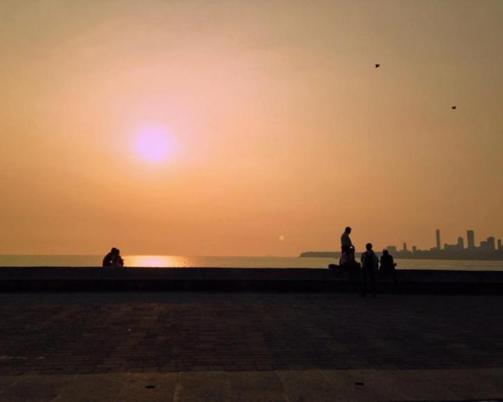 Couple watching the sunset on Chowpatty Beach.